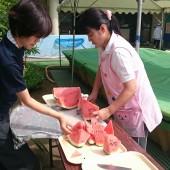 子どものゲーム中、先生はスイカを切り分けてます。どれを食べても同じ甘みが味わえる切り方にカットしています。
