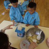 湯のみにラップを敷いてご飯を先生がよそいます。