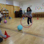 2つのグループに分かれて、フープでボールを上手に押して競争しました。