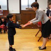 卒業式の後、担任の先生から修了証書を受け取りました。