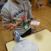 年長組・・・はりぼてのお面を製作中です。新聞紙と和紙を風船の上に何度も重ねて貼り付けています。