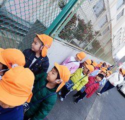 友達と手を繋いで歩いています。小学校を覗いていますね!