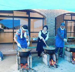 運動場で先生たちが、火をおこして煮込んでいます!